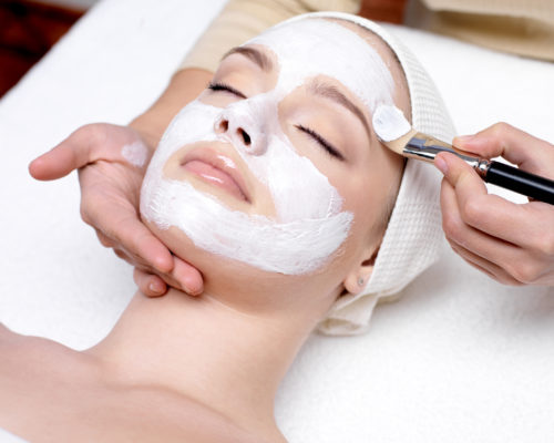 Beautiful young woman receiving facial mask at beauty salon - indoors